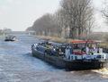 Schokland het kielzog van de  Manuela op weg naar de hoge vaste brug over het Van Starkenborghkanaal nabij Noord-Zuidhorn.