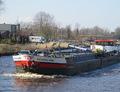 Schokland nadert de hefbrug over het Van Starkenborghkanaal nabij Noord-Zuidhorn.